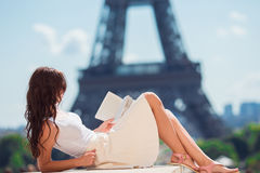 Beautiful woman reading book in Paris background the Eiffel tower Stock Photos