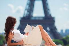 Beautiful woman reading book in Paris background the Eiffel tower Royalty Free Stock Image
