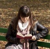 Beautiful woman reading book in park stock photos