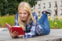 Beautiful woman reading book in park. Young beautiful woman reading book in park Stock Photography