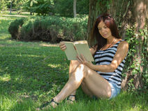 Beautiful woman reading a book. Beautiful woman with sexy legs reading in summer Royalty Free Stock Photo