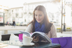 Beautiful woman reading book at sidewalk cafe Stock Image
