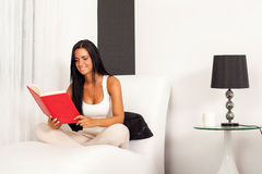 Beautiful woman reading a book. Beautiful woman sitting on the sofa and  reading a book Royalty Free Stock Images