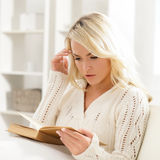 Beautiful woman reading a book thoughtfully in the morning Royalty Free Stock Photography