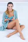 Beautiful woman reading e-book. Portrait of a beautiful young woman reading electronic book in bed Royalty Free Stock Images