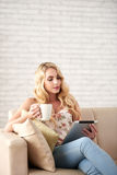 Beautiful Woman Reading at Home. Portrait of beautiful young woman reading from digital tablet sitting on comfortable sofa at home with cup of coffee Royalty Free Stock Images