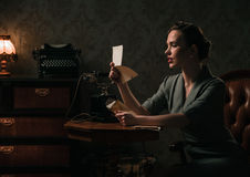 Beautiful woman reading letter in retro interior. Beautiful young woman in retro interior stock photos