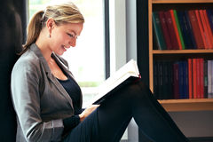 Beautiful woman reading in library. Beautiful woman reading in a library sitting comfortably on the floor with a delightful smile on her face as she enjoys her Royalty Free Stock Photo
