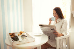 Beautiful woman reading morning paper. And drinking coffee Stock Photos