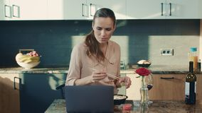 Beautiful woman reading news at house. Concentrated woman preparing to eat sushi. Beautiful woman reading news at laptop in luxury house. Concentrated woman stock footage