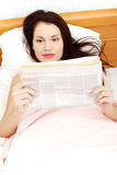 Beautiful woman reading a newspaper in bed. Stock Photos