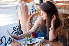 Beautiful woman reading a newspaper in the cafe Stock Image