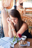 Beautiful woman reading a newspaper in the cafe Stock Images