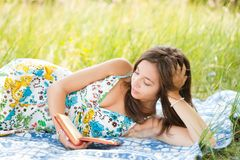 Beautiful woman reading outdoors. Beautiful young woman reading outdoor, lying on a blanket Stock Photography