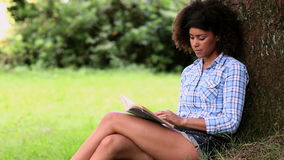 Beautiful woman reading in the park leaning against a tree stock video footage