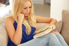Beautiful woman reading on a sofa Stock Photo