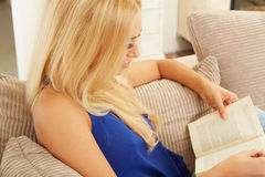 Beautiful woman reading on a sofa Royalty Free Stock Photography
