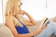 Beautiful woman reading on a sofa Royalty Free Stock Image