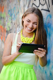 Beautiful woman reading on tablet pc at graffiti Stock Image
