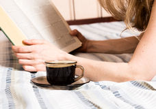 Beautiful woman reading a thick book lying on the bed, close-up coffee cup Royalty Free Stock Photos