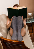 Beautiful woman reading a thick book lying on the sofa Royalty Free Stock Photos
