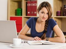 Beautiful woman reading and using a laptop stock photo