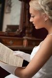 Beautiful woman reading vintage sheet music Stock Image