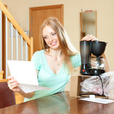 Beautiful woman reading  warranty card for new coffee machine  a Royalty Free Stock Photo