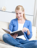 Beautiful woman reads the book lying on the sofa Stock Photography