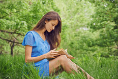 Beautiful woman reads a book in summer Stock Photos