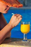 Beautiful woman ready to enjoy juice by the pool Stock Photography