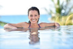 Beautiful woman realxing by the edge of swimming pool Royalty Free Stock Images