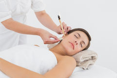 Beautiful woman receiving ear candle treatment at spa center Royalty Free Stock Photography