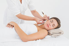 Beautiful woman receiving ear candle treatment at spa center Royalty Free Stock Image