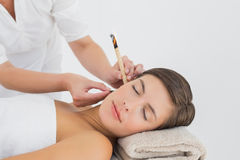 Beautiful woman receiving ear candle treatment at spa center Stock Image