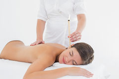 Beautiful woman receiving ear candle treatment at spa center Stock Images