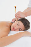 Beautiful woman receiving ear candle treatment at spa center Royalty Free Stock Images