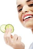 Beautiful woman receiving facial mask of cucumber Stock Photos