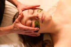 Beautiful woman receiving a facial massage in a spa. Stock Photos