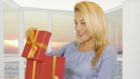 Woman receiving gift in red box on window background with evening sunset in sea. Beautiful woman receiving gift in red box on window background with evening stock video