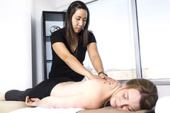 Beautiful woman receiving massage from physical therapist Stock Images