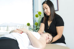 Beautiful woman receiving massage from physical therapist Stock Photos