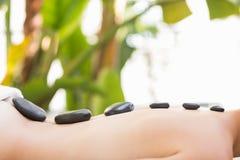 Beautiful woman receiving stone massage at spa center Stock Image