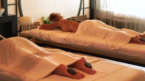 Beautiful woman receiving stone massage in spa resort. Young woman relaxing while back massage with hot stone. Spa stock video