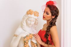 Beautiful woman in red with antique statue Royalty Free Stock Photography