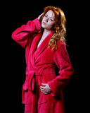 Beautiful woman in a red bathrobe Stock Photography
