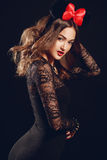 A beautiful woman with a red bow on a dark background. Royalty Free Stock Image