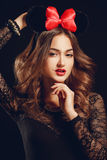 A beautiful woman with a red bow on a dark background. Royalty Free Stock Photo