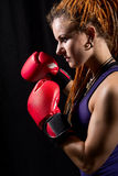 Beautiful woman with red boxing gloves, dreadlocks on a black ba Royalty Free Stock Photos