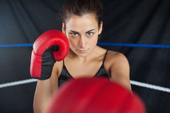 Beautiful woman in red boxing gloves in the ring Stock Photo